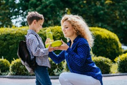 Positive caucasian mother in blue shirt giving school lunch and bottle with wather to her little pupil son outdoors in sunny morning. Back to school.education, caring, single parent support concept.