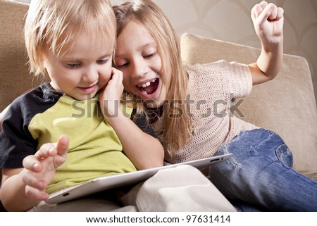 positive caucasian school girl and small boy  is with tablet computer at home