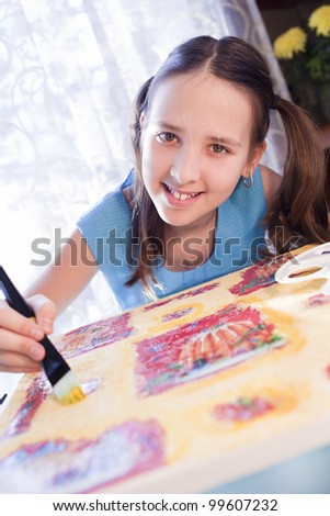 positive caucasian school girl are painting at home