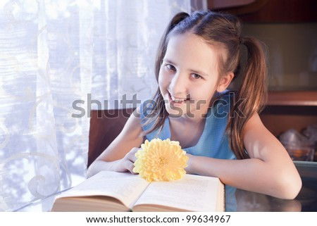 positive caucasian school girl with open book at home - stock photo