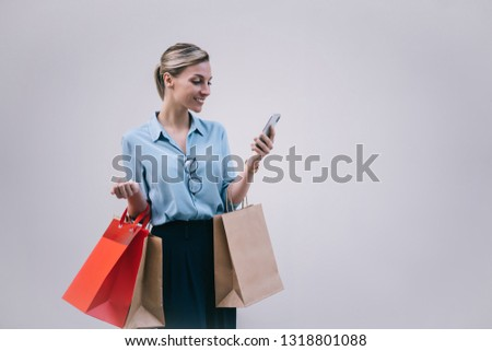 Positive caucasian shopper in stylish wear holding paper bags and enjoying online messaging via smartphone application, happy hipster girl chatting near promotional background on publicity area