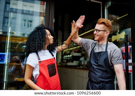 Positive caucasian waiter and cheerful african american waitress in aprons working in team and giving five each other for great job in common cafeteria standing outdoors.Partnership concept