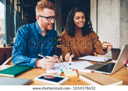 Positive caucasian young man and cheerful dark skinned student watching together funny webinar during e-learning on modern laptop computer connected to wireless 4G internet sitting in university