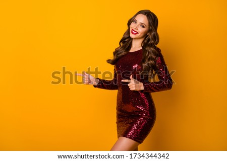 Positive cheerful sweet pretty girl point index finger copyspace demonstrate advert promotion recommend suggest select wear red good look clothes isolated over bright shine color background