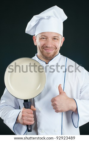 Positive chef with a frying pan gesturing OK and looking at camera