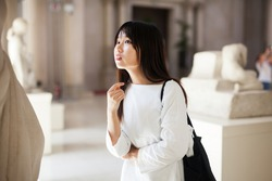 Positive chinese girl with interest looking around at ancient sculptures in modern museum