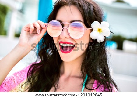 Positive close up portrait of pretty happy smiling woman with stylish beach outfit bikini and sunglasses, exotic tiare flower on her hairs, toned soft colors, vacation mode.