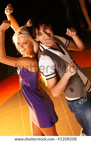 Positive couple dancing at disco and looking at camera