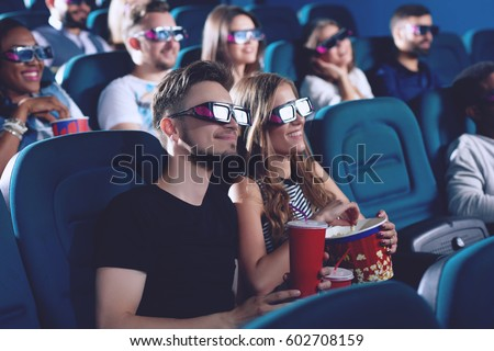Positive couple drinking cola and eating popcorn in cinema.