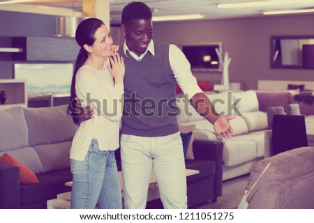 Positive couple is choosing new furniture for interior their room in the store