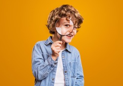 Positive curious schoolboy in casual wear looking at camera through magnifier while standing against bright orange background