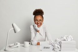 Positive curly Afro American female entrpreneur works on project work, sits at white office desk with some objects, has business planing, smiles happily, has coffee break. Monochrome backround.