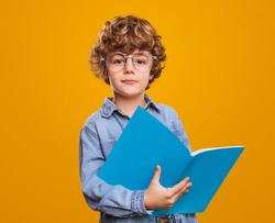 Positive curly haired elementary school nerd boy in eyeglasses holding open textbook and looking at camera against yellow background