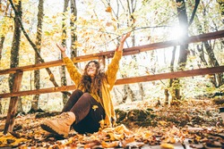 Positive curly haired woman in yellow sweater throwing dry leaves in picturesque autumn forest with colorful trees on sunny day.