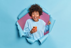 Positive curly haired woman smiles broadly uses smartphone reads funny news on website reacts on something awesome and pleasant dressed in casual jumper poses in ripped hole. Staying always in touch