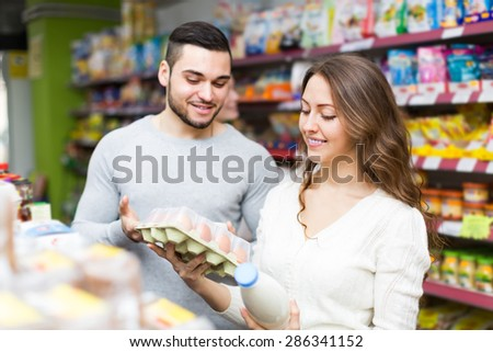 Positive customers choosing milk and eggs at store and smiling. Focus on girl