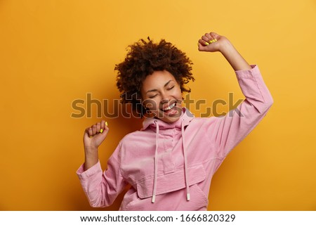 Positive dark skinned curly woman keeps hands raised in air, dances carefree, feels lively and upbeat, wears velvet hoodie, isolated over yellow studio background, throws party, enjoys freedom