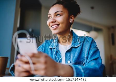 Positive dark skinned hipster girl listening motivation audio record feeling good from information heard via headphones, happy african female meloman enjoying music from media app on cellphone