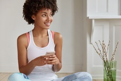 Positive dark skinned hipster updates notification on new cell phone, sits on floor with legs crossed, connected to wifi at home, looks aside, copy space. Woman shops online, enjoys discounts