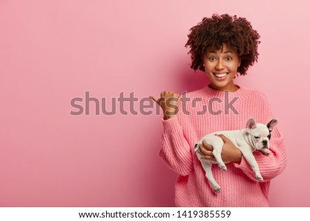 Positive dark skinned lady points thumb away, wears casual jumper, holds sleeping dog, being caring hostess, shows direction to animal shop, isolated over pink background. Pedigree puppy with owner #1419385559