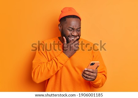 Positive dark skinned man giggles positively concentrated at smartphone screen watches funny video in internet or laughs over received message dressed in casual bright clothes isolated on orange wall ストックフォト ©