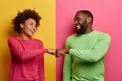 Positive dark skinned young woman and man bump fists, agree to be one team, look happily at each other, celebrates completed task, wear pink and green clothes, pose indoor, have successful deal