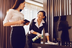 Positive delighted chambermaid polishing furniture