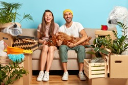 Positive delighted woman and man play with their favourite dog, pose on sofa, rejoice day of moving in new apartment, surrounded with different boxes, indoor plants. Family, relocation and fun concept