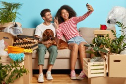 Positive diverse couple laugh and have fun, take selfie with modern cell phone, have rest during unpacking personal belongings, have moving day, buy new apartment, sit on sofa together with dog
