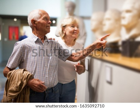 Positive elderly couple looking at exhibits on exposition of museum
