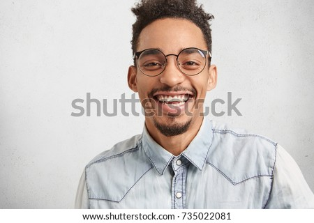 Positive emotions, facial expressions and happiness concept. Joyful man with oval face, mustache and beard smiles broadly, shows white perfect teeth, hears funny story or anecdote told by best friend - Shutterstock ID 735022081