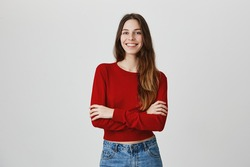 Positive emotions, good vibes. Portrait of young cute female student with long dark hair in casual hip outfit smiling, crossing hands, having photo session for graduation album