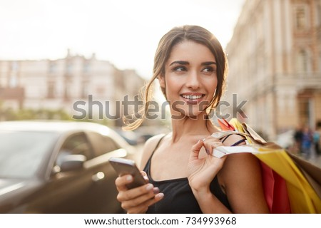 Positive emotions. Lifestyle concept. Close up of young charming dark-haired caucasian woman in black dress smiling with teeth, looking aside with relaxed expression, chatting with boyfriend on phone