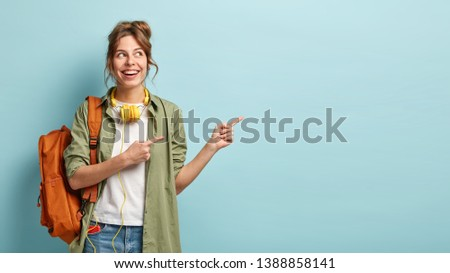 Positive European female teenager uses modern technologies for entertainment, points aside on free space, dressed in loose shirt and jeans, carries backpack, promotos something, poses indoor