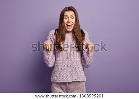 Positive European lady with happy look, offers to look down, points with both fore fingers, dressed in casual jumper, isolated over purple background. Overjoyed seller advertises product indoor Foto stock ©