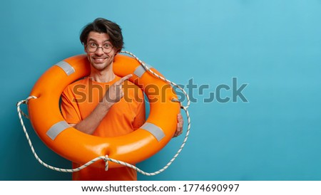 Positive European man lifesaver poses with inflated orange life ring, indicates at empty space, shows way to sea or swimming pool. Lifeguard on duty holds rescue circle. Safety beach holiday. Stockfoto ©