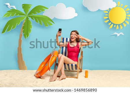 Positive European woman relaxes in deck chair, makes selfie on modern cell phone, shows peace sign, shares pics with friend in social networks, uses sunscreen lotion for good sunbathing. Summer time