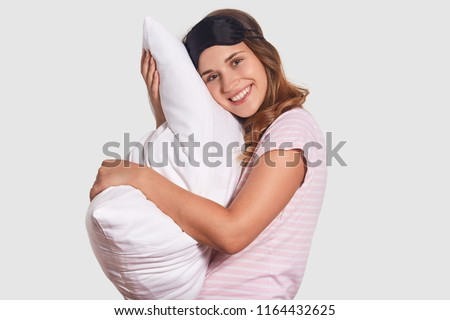 Positive European woman with friendly smile leans at white pillow, wears sleep mask and pyjamas, rejoices having good rest at night, stands sideways against white wall. Good morning concept.