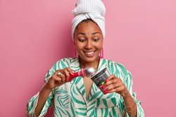 Positive excited dark skinned young woman has temptation to eat sweet delicious cold ice cream, holds special spoon, smiles happily, wears domestic robe and bath towel on head, stands indoor
