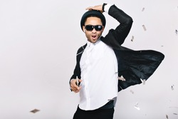 Positive excited handsome guy in suit, hat, black sunglasses having fun on white background. Listening to music through headphones, dancing, singing, celebrating party, happiness