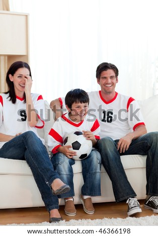 Positive family watching football match on television