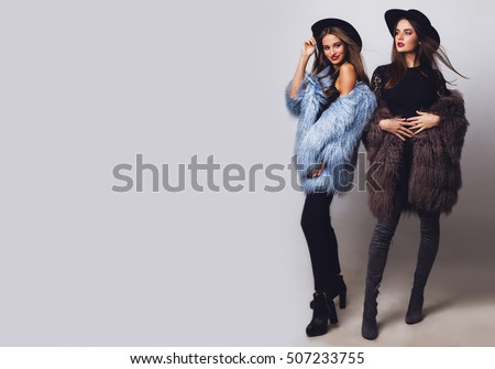 Positive fashion portrait of two girls, best friends posing indoor on grey background wearing winter fluffy coat, black casual hat. Fashionable clothes.  Sisters walking. Space for text. Full length .
