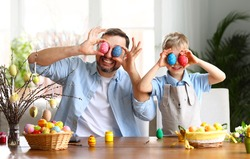 Positive father and cute boy sitting at table and covering eyes with colorful painted eggs while preparing for Easter holiday and having fun at home
