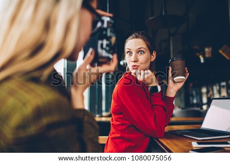 Positive female blogger with funny grimace on face posing on vintage camera having fun during coffee break.Hipster girl focusing to make photo of best friend for publication in social networks