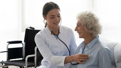 Positive female caregiver visit smiling senior disabled grandmother check heart rate, young woman doctor use statoscope do regular checkup of old lady patient at home, elderly healthcare concept