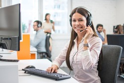 Positive female customer services agent with headset working in call center