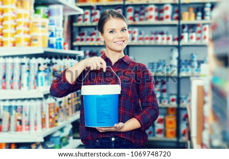 positive female designer is holding paint for redecorate room in the store.