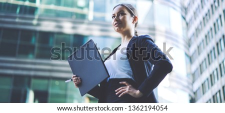 Positive female entrepreneur in formal wear from designer feeling confident and enjoying good day on urban setting, successful caucasian business woman with folder in hand standing on publicity area