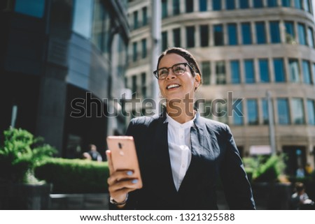 Positive female entrepreneur smiling outdoors enjoying weather on break during sunny day, successful busineswoman in formal wear holding modern smartphone gadget while using banking application