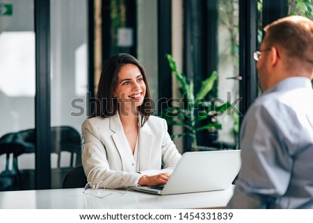 Positive female financial advisor on a meeting with a client.